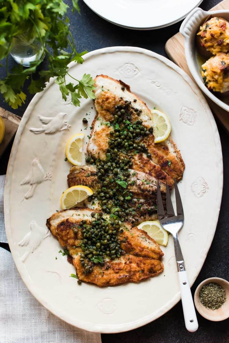 Sole Meunière topped with capers, lemons, and parsley on a serving platter.