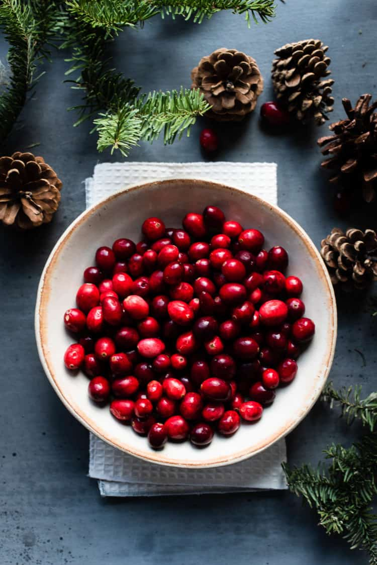 A bowl of fresh cranberries on a grey table with pine cones and greens.