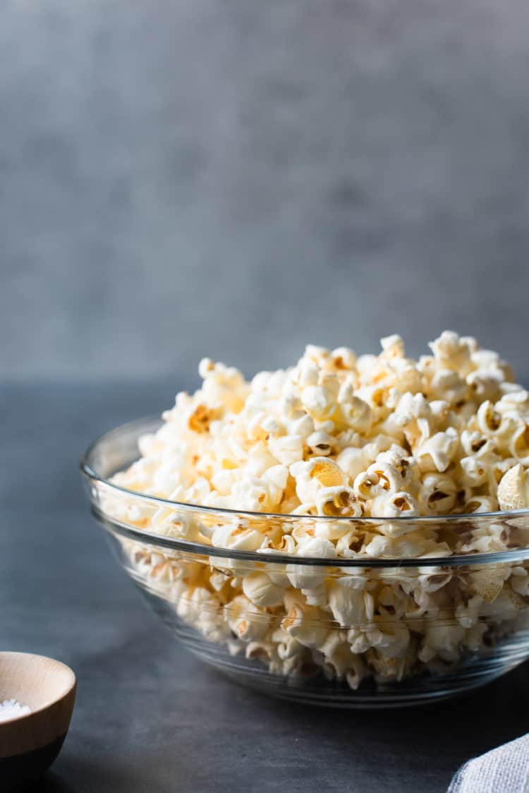 Glass bowl of homemade stovetop popcorn on grey surface.