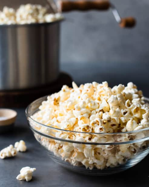 Glass bowl of homemade stovetop popcorn with metal pot in background.