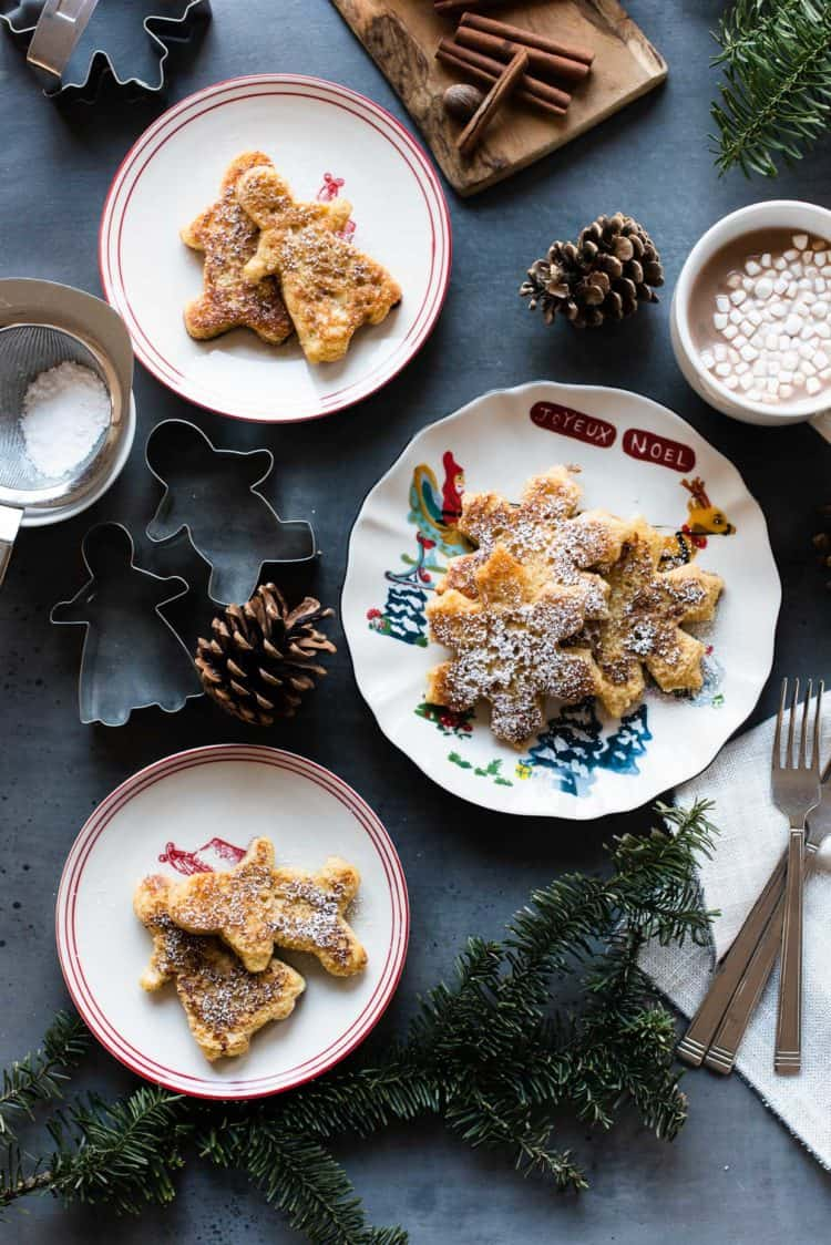 Holiday plates with gingerbread french toast dusted in powdered sugar.