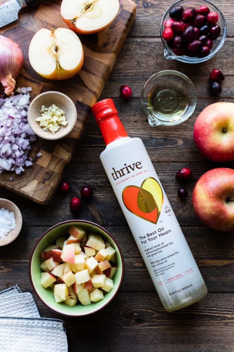 Thrive Culinary Algae Oil on a wooden table with ingredients for Roast Pork Loin with Apple Chutney.