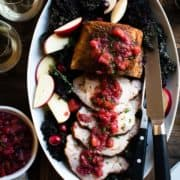 Roast Pork Loin with Apple Chutney sliced on a platter with fresh apple slices on a bed of kale. Glasses wine and a bowl of chutney on the side.