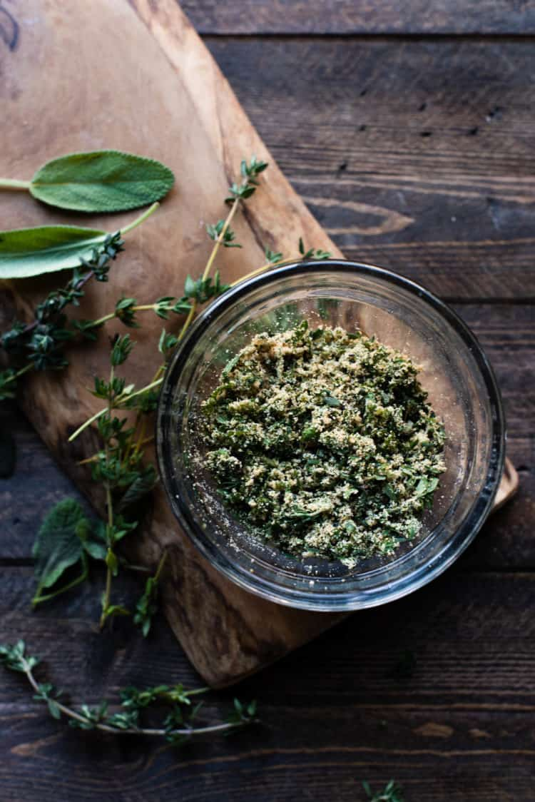Herb blend for Savory Herb Stuffing Bread in a glass bowl on a wooden table.