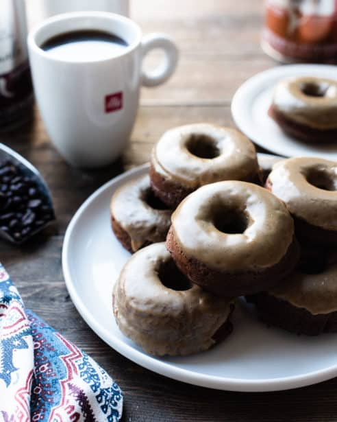 A stack of Coffee-Glazed Baked Chocolate Doughnuts on a white plate with mugs of illy coffee.