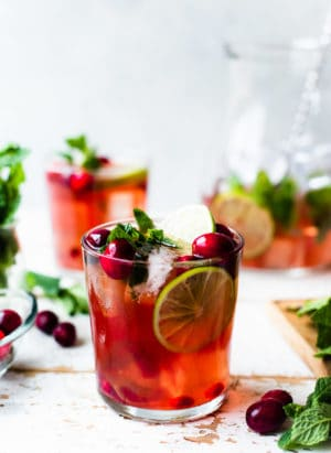 Cranberry Pomegranate Mojito in a glass garnished with limes, cranberries, pomegranate arils and mint.