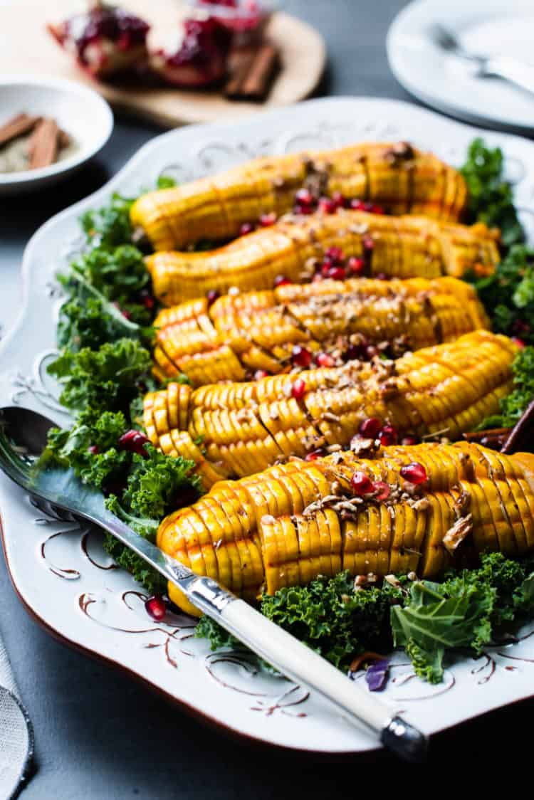 Maple Cinnamon Hasselback Delicata Squash on a platter on a bed of kale.