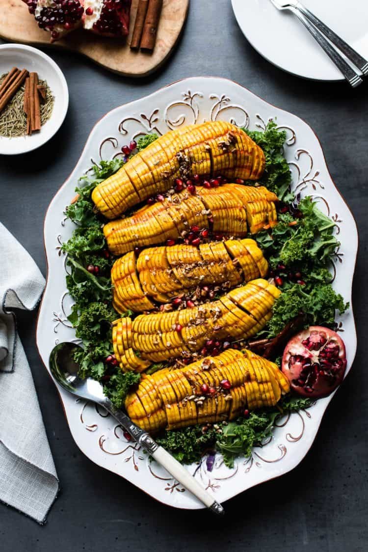 Maple Cinnamon Hasselback Delicata Squash on a platter served with a kale salad.