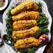 Maple Cinnamon Hasselback Delicata Squash on a bed of kale salad with pomegranates and pecans.