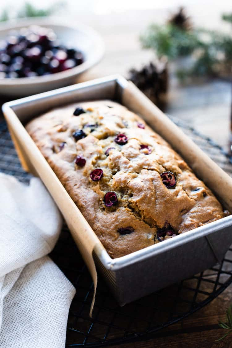 Maple Glazed Cranberry Bread freshly baked in a loaf pan with cranberries in the background.