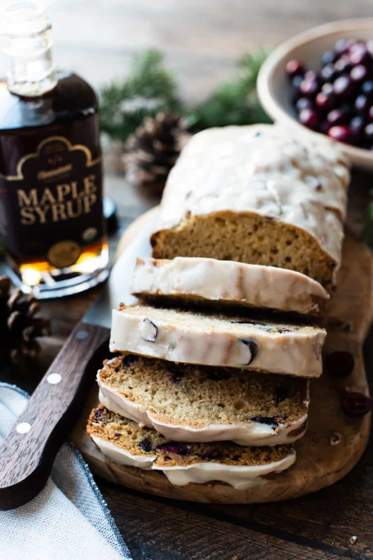 A sliced loaf of Maple-Glazed Cranberry Bread with maple syrup in the background.