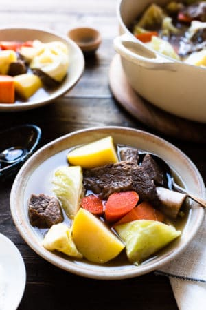 A bowl of Beef Nilaga (Filipino Beef and Vegetable Soup) made in the Instant Pot. Chunks of beef, short ribs, potato, cabbage, carrots, and sweet potato in a bowl.