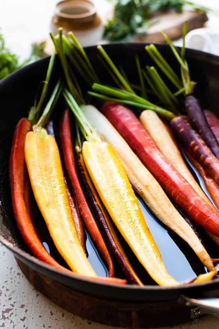 Carrots in pan with honey glaze for Honey-Spice Glazed Carrots.