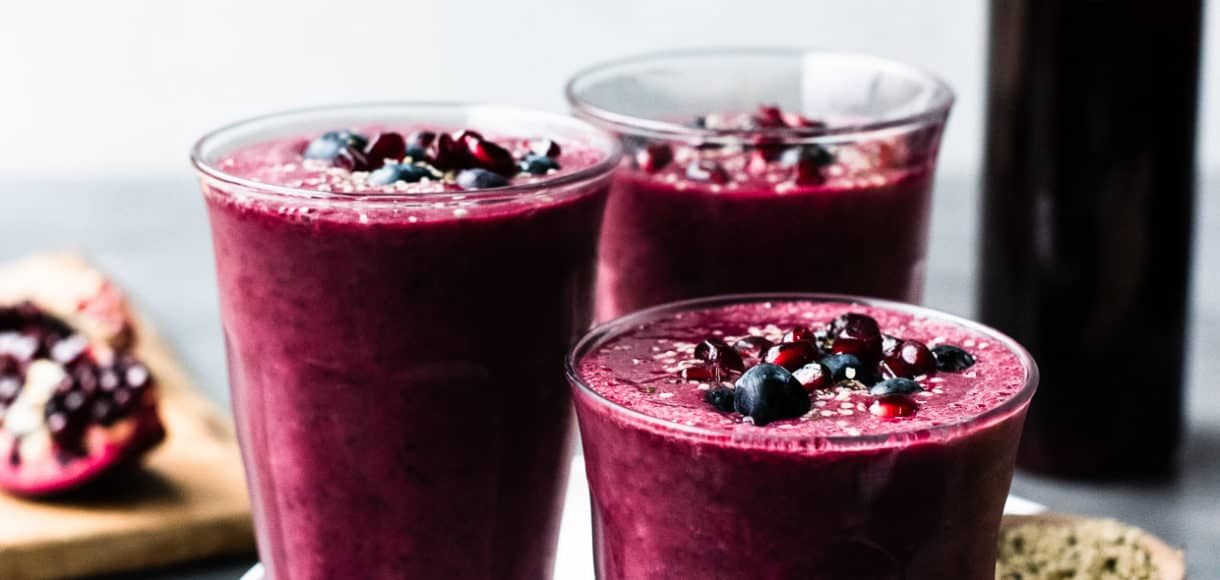 Pomegranate Berry Smoothies topped with blueberries and pomegranate arils.