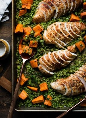 Sliced chicken breast on a sheet pan with broccoli rice and sweet potatoes.
