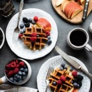 Apple Oatmeal Blender Waffles topped with fresh berries, slices of apple on white plates.