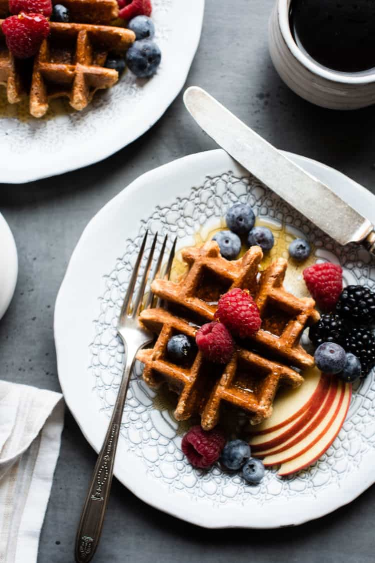 Apple Oatmeal Blender Waffles  on a white plate with fresh berries and apples.