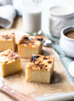 Slices of Cassava Cake on a board with coffee in the background.