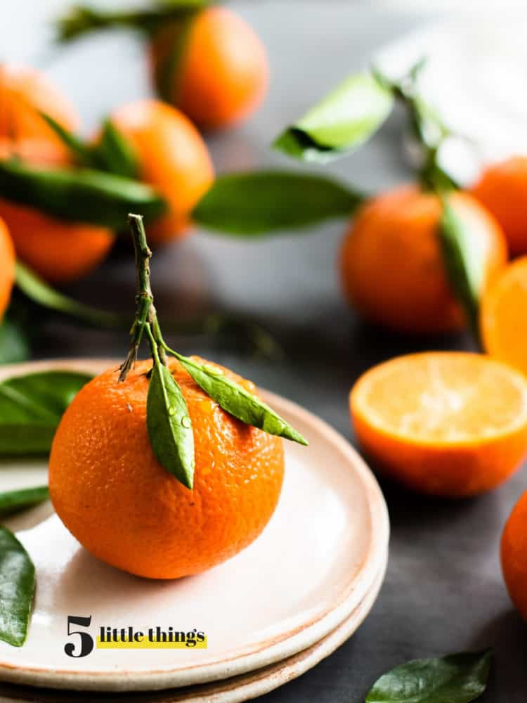 mandarin orange on a plate with oranges in the background