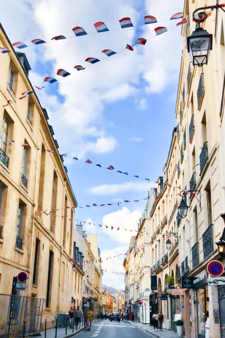 French flags hanging between buildings in Le Marais Paris, France.