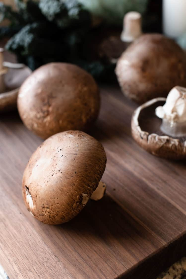 Portobello mushrooms on a cutting board.