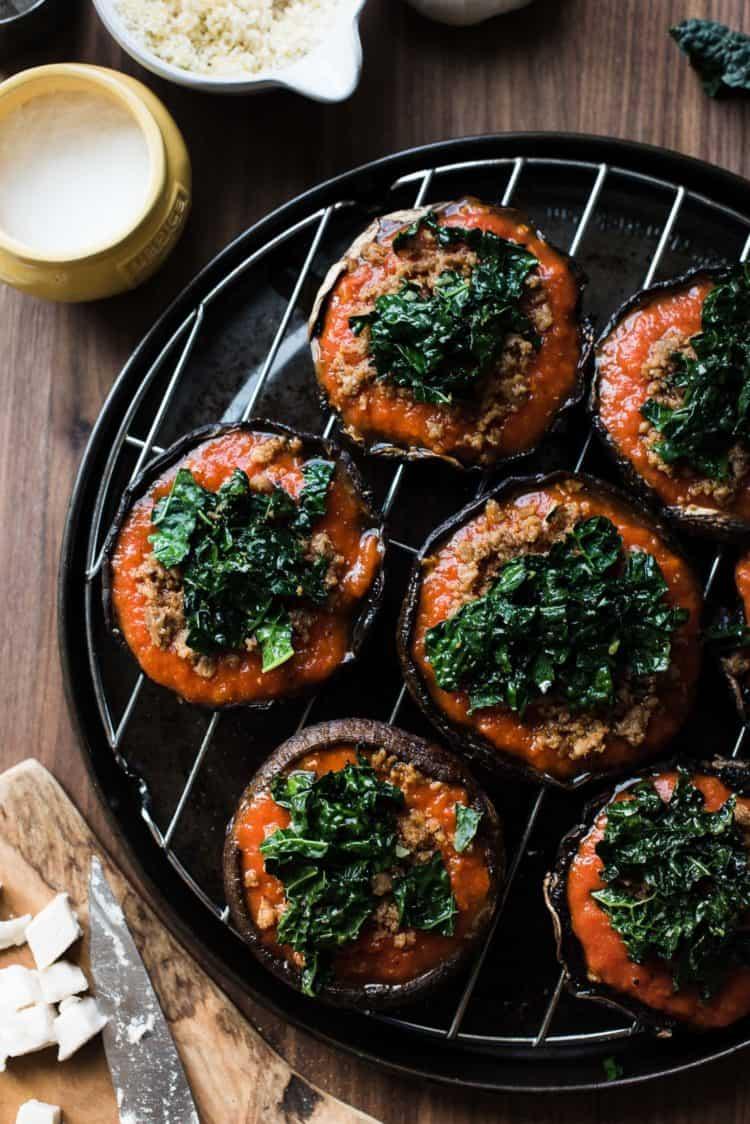 Preparing stuffed portobello mushrooms with marinara sauce and garlicky kale.