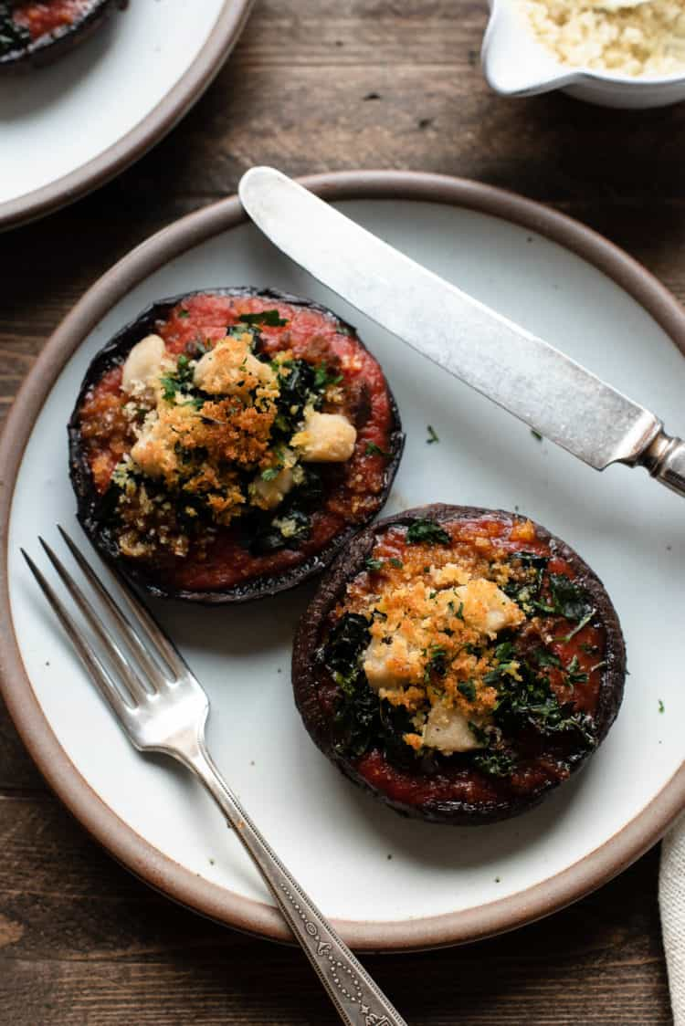 Stuffed Portobello Mushrooms with Garlicky Kale served on a plate.