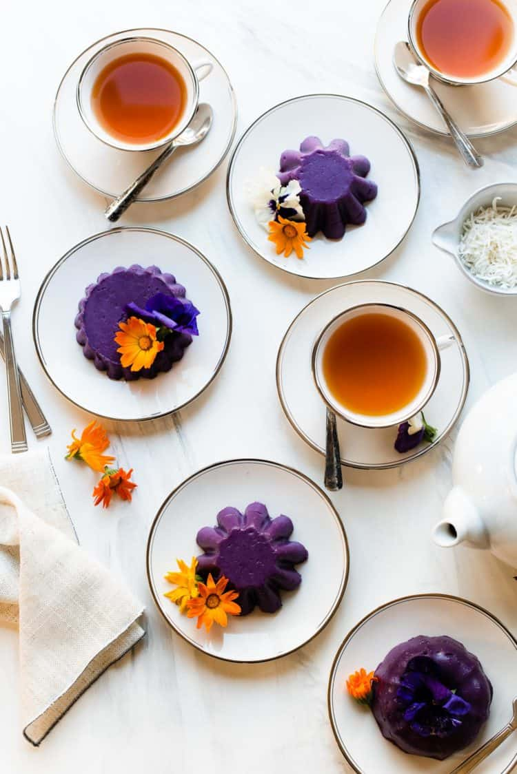 Ube Halaya served with edible flowers on white plates and served with tea.