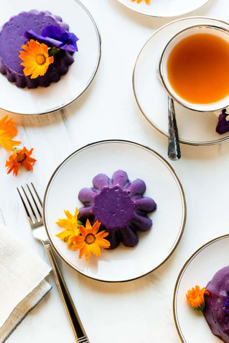 Ube Halaya molded into individual cakes, garnished with edible flowers.