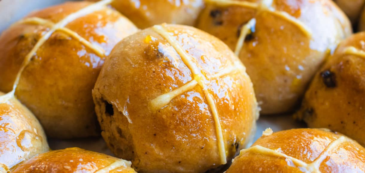 Glazed hot cross buns on a baking sheet. Overnight vegan recipe.