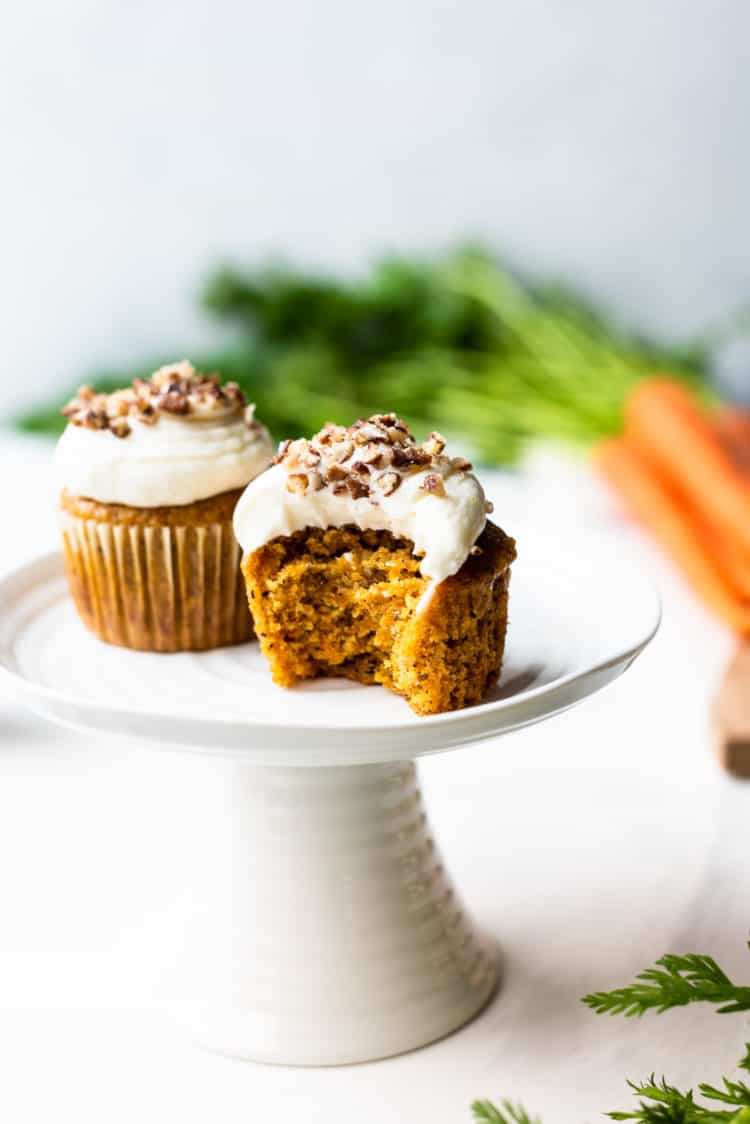 Carrot cake cupcakes with cream cheese frosting with bite taken out.
