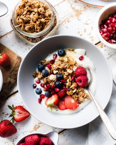 Homemade Almond Butter Granola with yogurt and berries in a bowl.