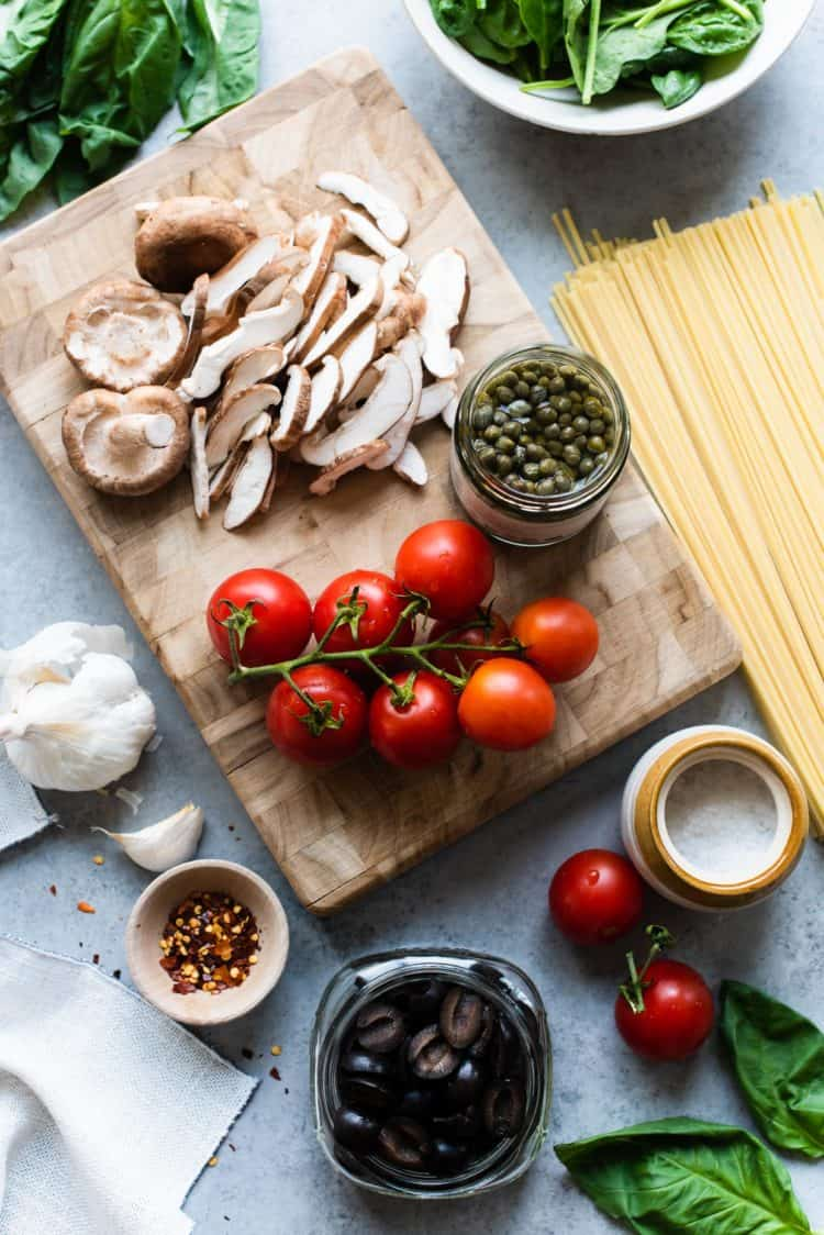 Tomatoes on the vine, sliced mushrooms, and a glass jar of capers on a wooden cutting board.