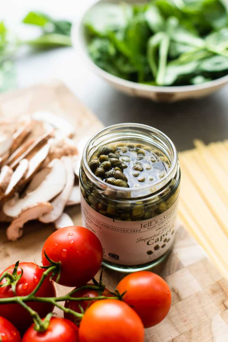 Jar of capers surrounded by sliced mushrooms and cherry tomatoes.