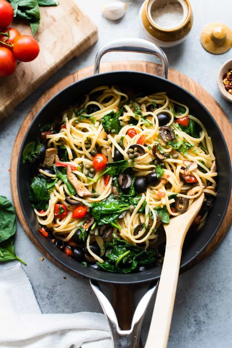 Vegetarian Pasta Puttanesca in a skillet on a wooden surface.