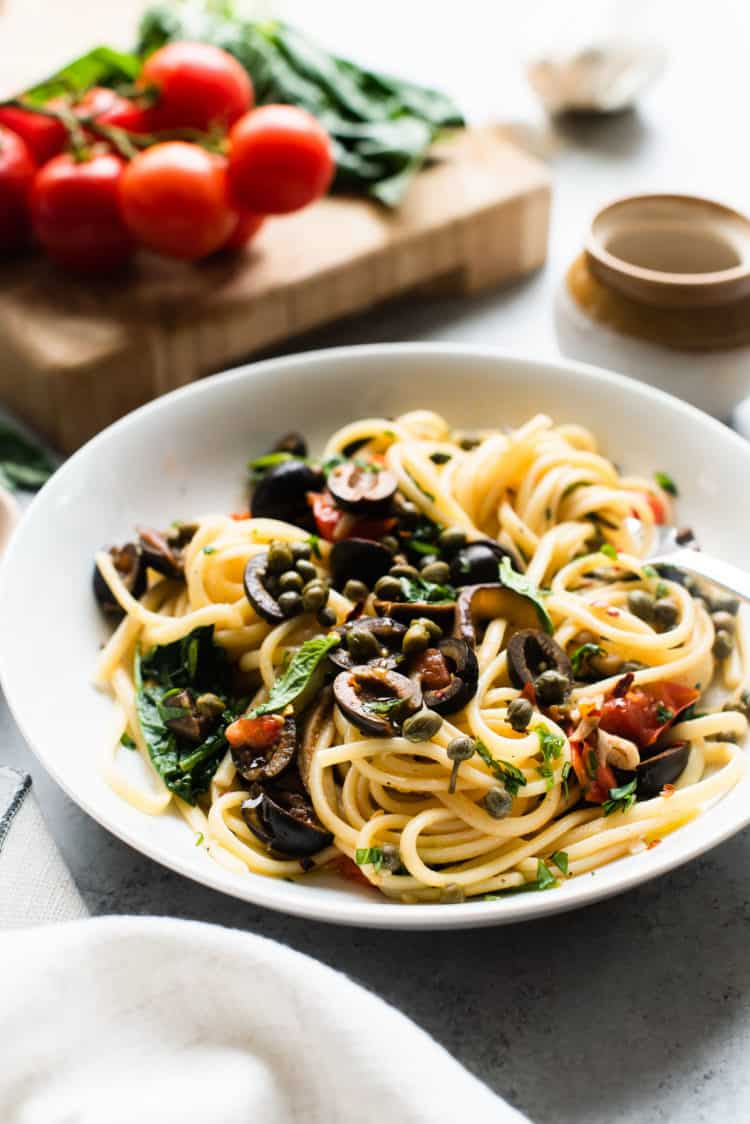 White dish filled with Vegetarian Pasta Puttanesca garnished with capers and sliced olives.