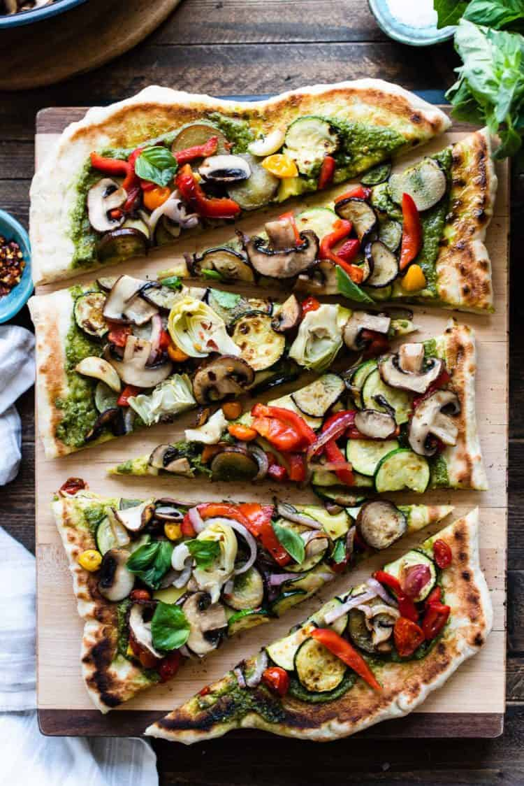 Slices of grilled vegetable pizza on a wooden cutting board.