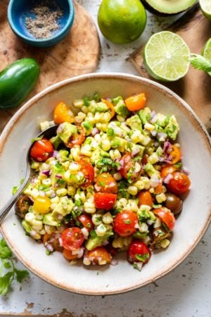 A healthy Avocado Corn Tomato Salad in a cream colored serving bowl.