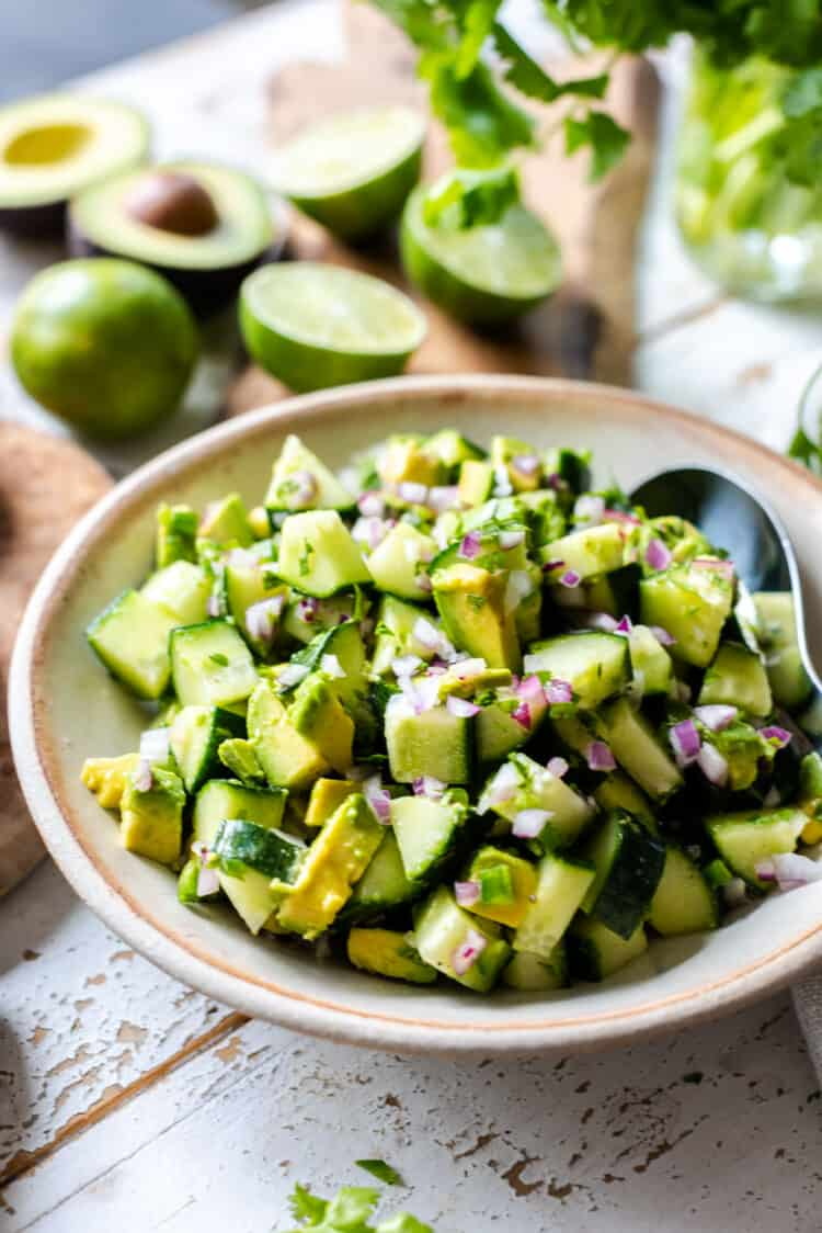 Avocado Cucumber Salad in a serving bowl with limes and avocados in the background.