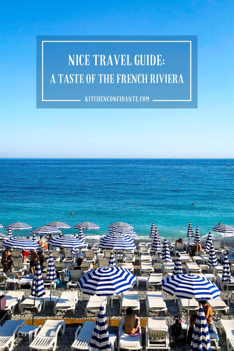 Seaside beach with blue and white striped umbrellas in Nice, France, part of Nice Travel Guide.