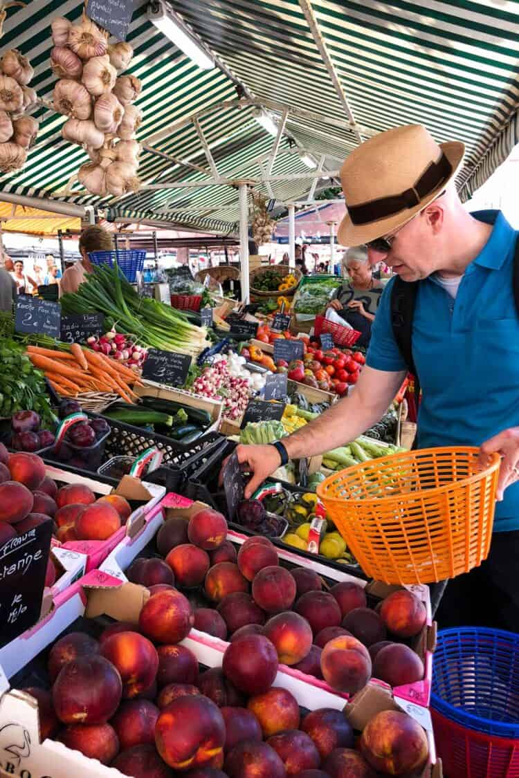 Shopping for fruits and vegetables at Marché aux Fleurs Cours Saleya, Nice, France.