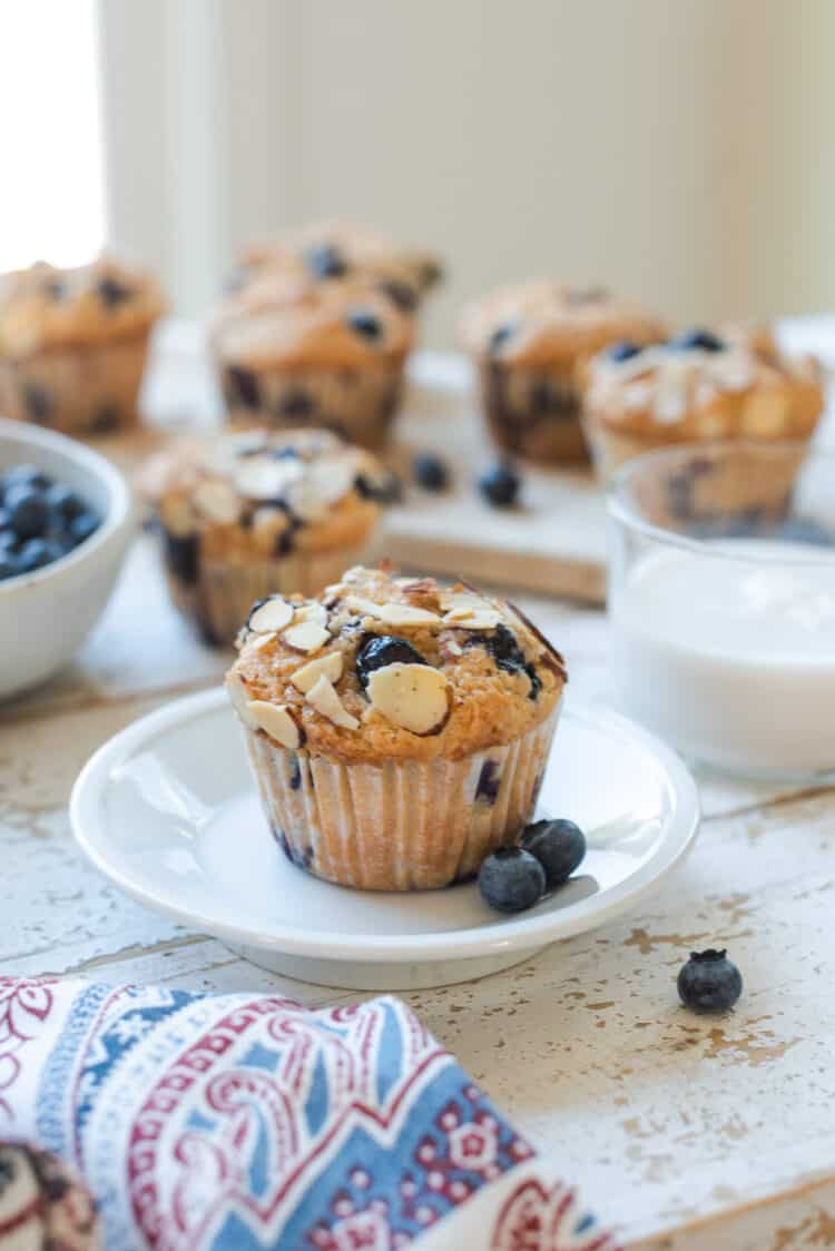 Blueberry Almond Butter Muffins on a white plate with milk in the background.