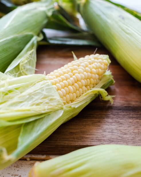 Corn on the cob cooked in microwave, peeling husk