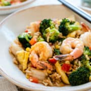 Spicy Shrimp Fried Rice in a cream bowl with chopsticks.
