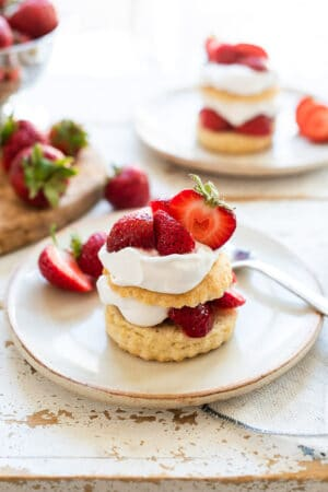 Vegan strawberry shortcake with layers of biscuit, strawberries and coconut whipped cream on a cream colored plate.