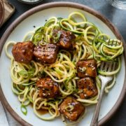 Plate of zucchini noodles (zoodles) topped with sweet and spicy crispy tofu, garnished with scallions and sesame seeds.