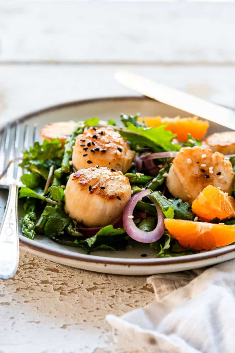 Pan Seared Scallops in a white dish over a bed of kale, asparagus, and fresh slices of tangerine.