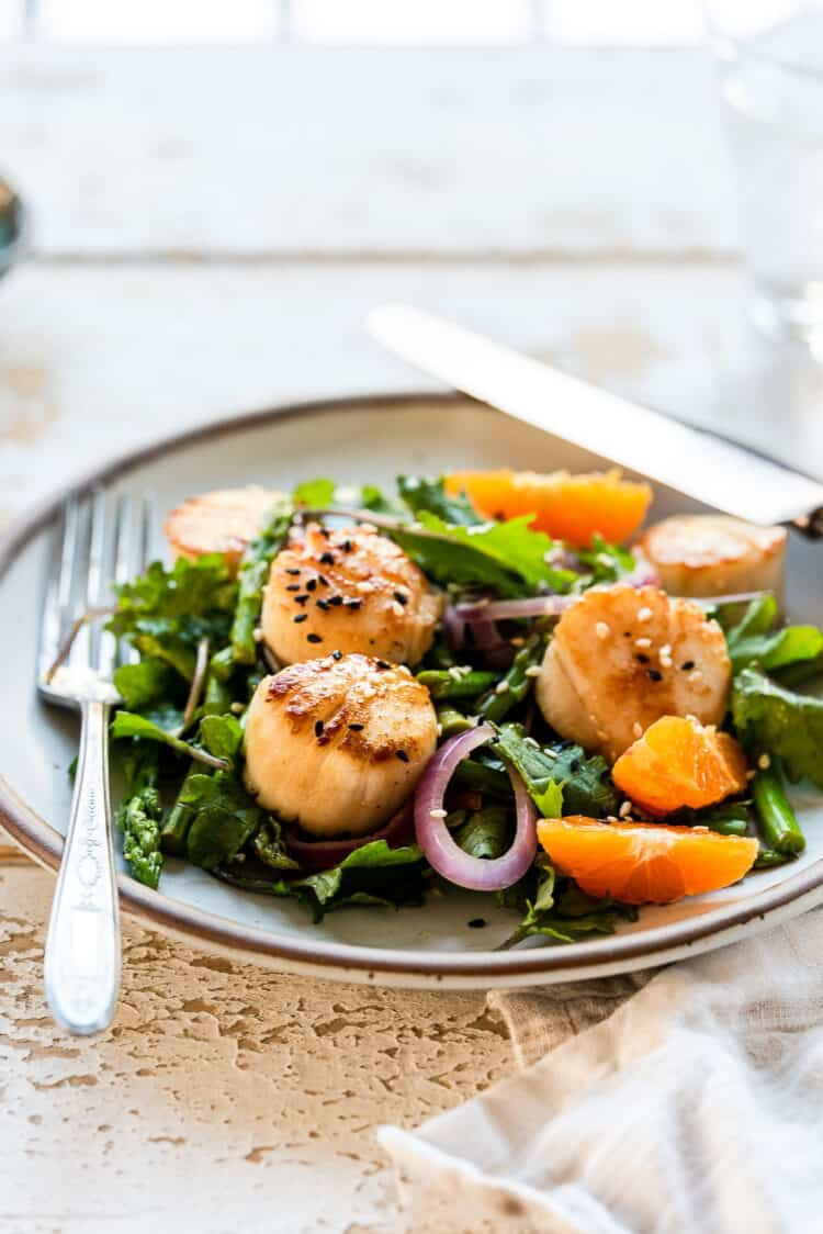 Pan-Seared Scallops with Warm Asparagus, Kale and Tangerine Salad on a cream colored plate.