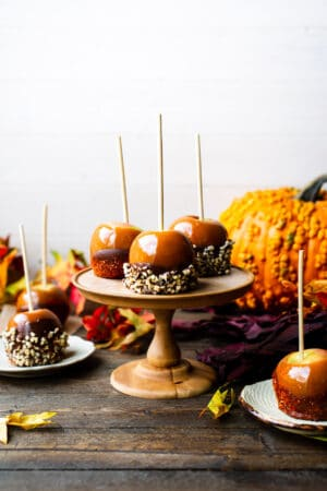 Double Dipped Chocolate Caramel Apples on a cake stand surrounded with pumpkins.