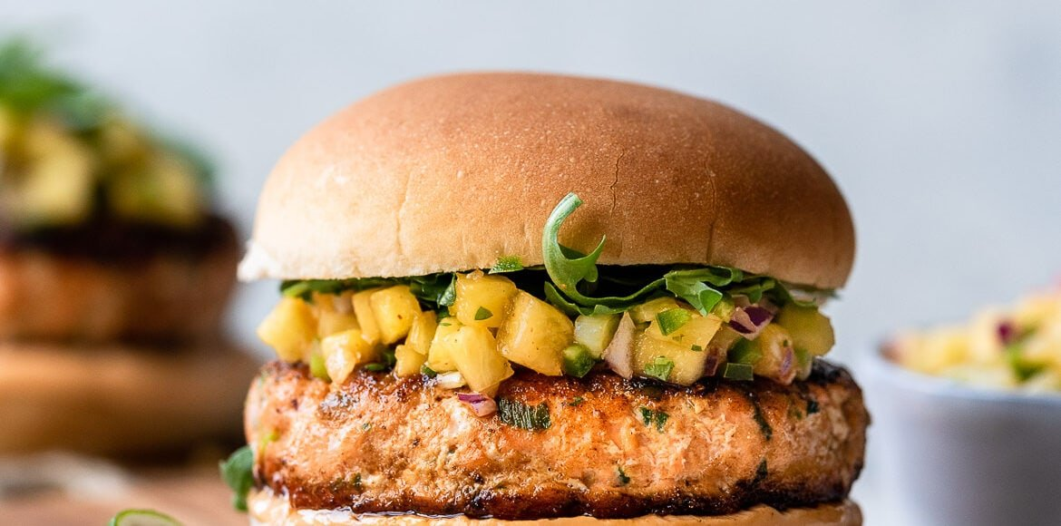 Thai Salmon Burger served on a bun with sriracha aioli and pineapple salsa on a wooden board.